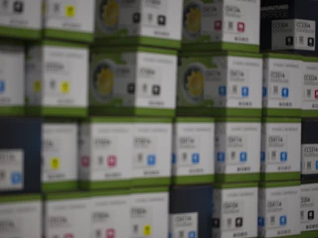 Ściana zastawiona pudełkami z kartridżami do drukarki