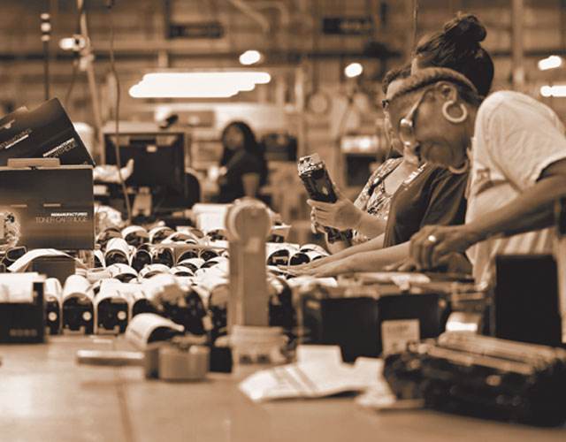A group of workers pack remanufactured toner cartridges on the assembly line in the early days of Static Controls cartridge remanufacturing operations